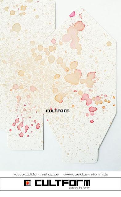 Die Hausbox von Cultform. Ein eindrucksvolles und doch einfaches DIY: kleine Geschenke individuell modern verpacken im aktuellen Watercolor-Trend: rot/orange Farbsprenkel auf dem Bastelbogen