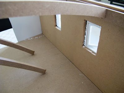 Inside of a half-built dolls' house shed, showing that the windows don't fit the full depth of the wall.