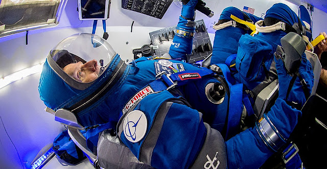 "Former astronaut Chris Ferguson sits inside a Starliner mock-up while wearing the new ""Boeing Blue"" spacesuit. Photo Credit: Boeing"