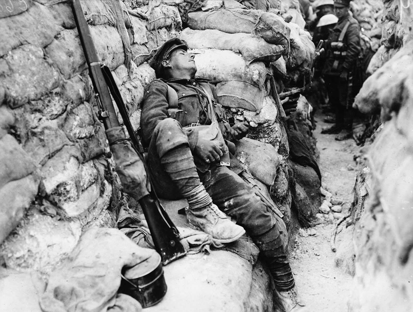 Soldier's comrades watch him as he sleeps, near Thievpal, France. Soldiers are standing in a very deep, narrow trench, the walls of which are entirely lined with sandbags. At the far end of the trench a line of soldiers are squashed up looking over each others' shoulders at the sleeping man.