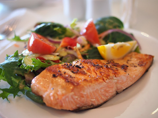 Salmon steak and green salad on a white plate.