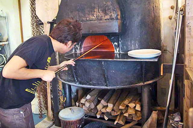 Chef placing a vegetarian pizza in wood-burning oven, Ukauka