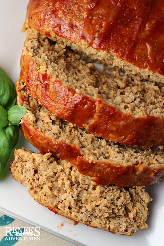 The Best Ground Turkey Meatloaf on a platter with basil to the side overhead view sliced from loaf