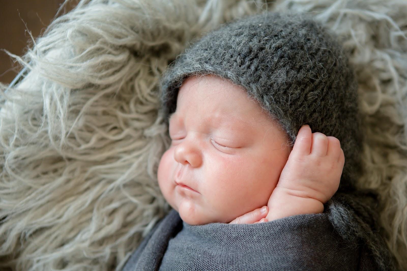 newborn baby boy in gray swaddle