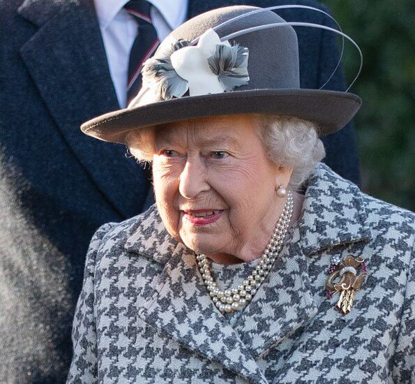 Queen Elizabeth wore a grey and white coat with a matching hat with grey and white flowers. The Queen traditionally spends the winter holiday