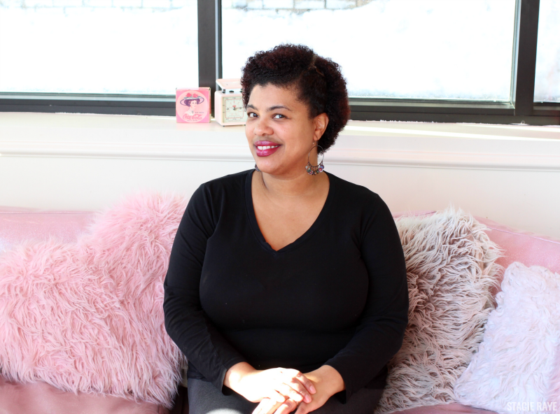 a woman sitting on a pink couch