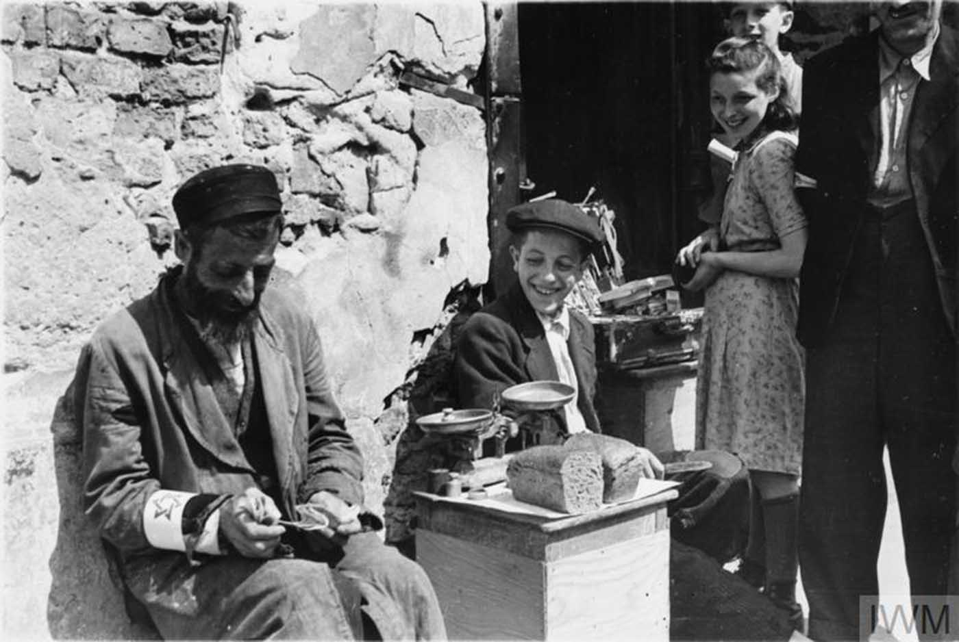 A Jewish man selling his bread allowance in the street of the ghetto, summer 1941.