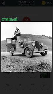 Старый автомобиль на дороге и сверху сидит парень держа в руках книгу