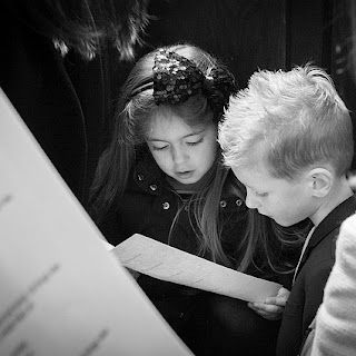 A girls shares her hymn sheets with a boy, photo is in black and white