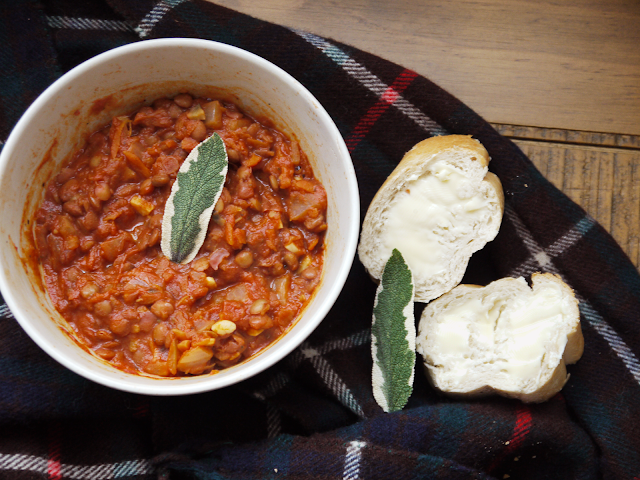 a bowl of lentil bolognese topped with sage leaves and a side of buttered baguette