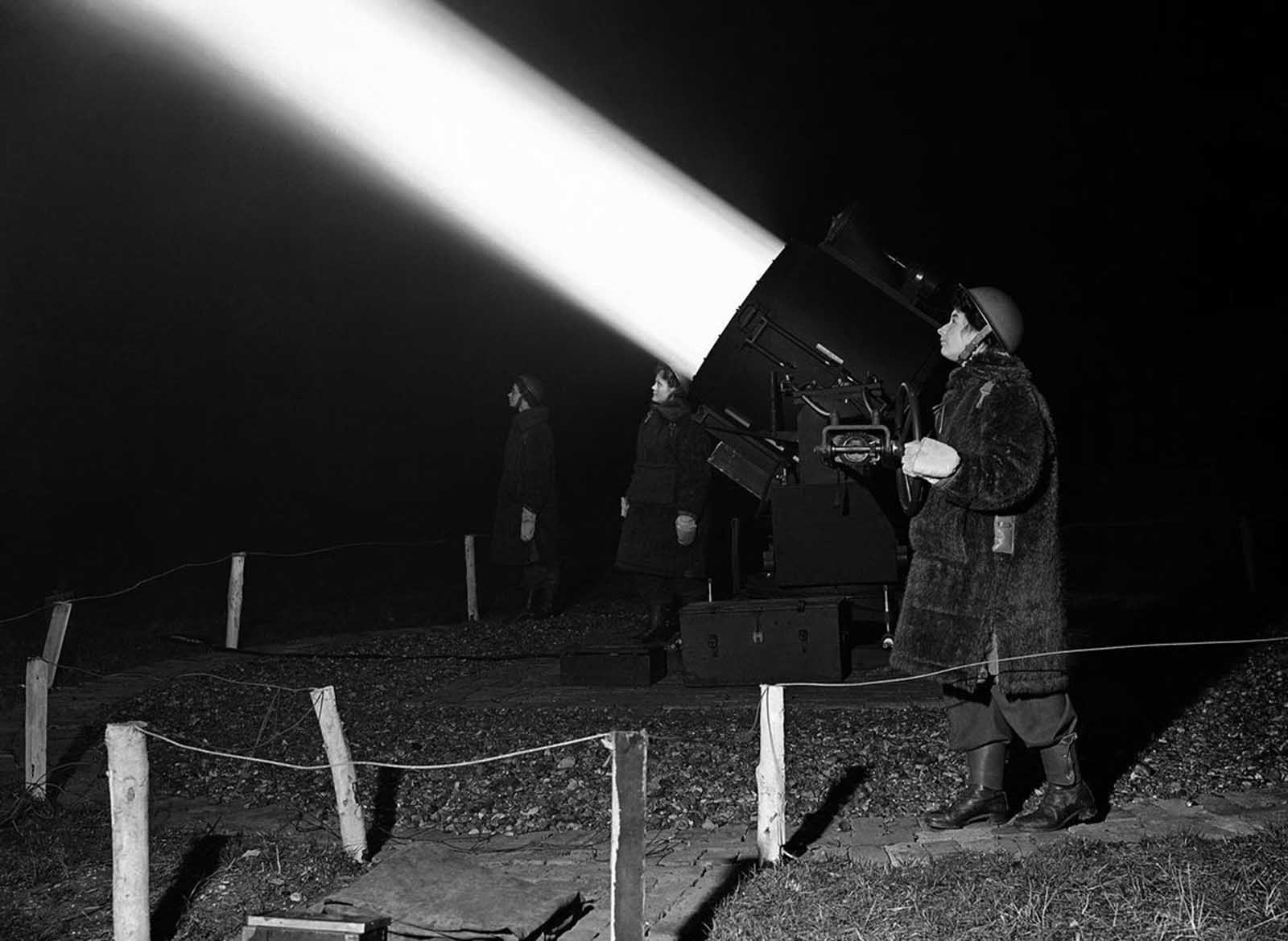 An Auxiliary Territorial Service girl crew, dressed in warm winter coats, works a searchlight near London, on January 19, 1943, trying to find German bombers for the anti-aircraft guns to hit.