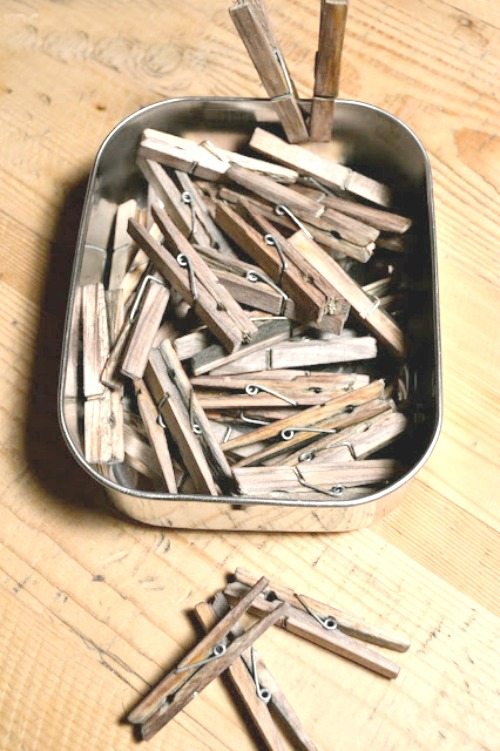 Pile of clothespins and container of aged clothespins