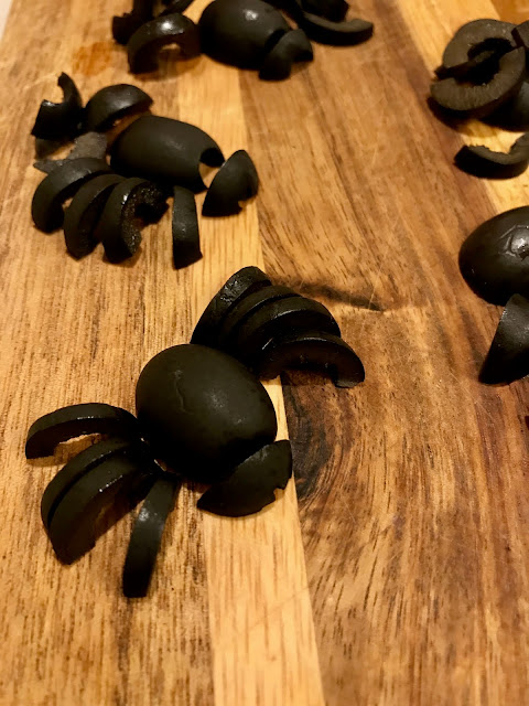 Black olive spiders being assembled on a cutting board.