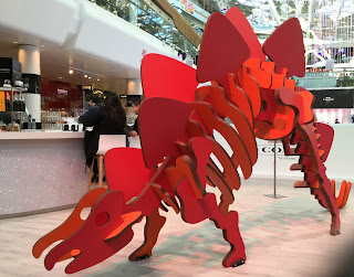 Pic of red stegosaurus with people sitting at bar behind
