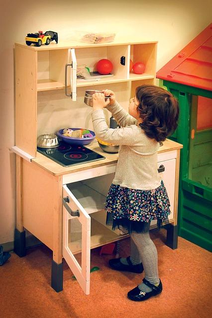 Mädchen spielt mit einer Kinderküche