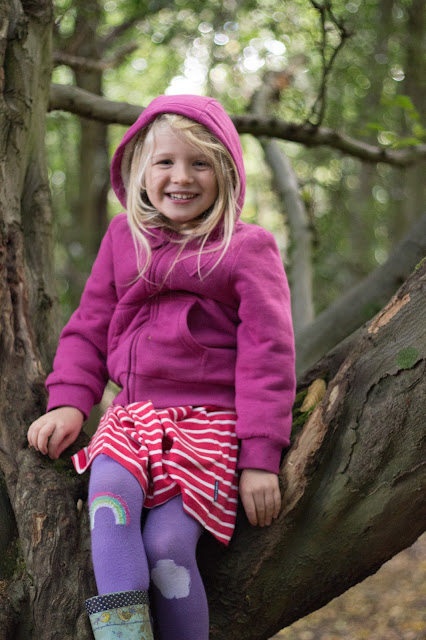 A girl in winter clothes: thick cardigan, tights and wellies sitting in a tree