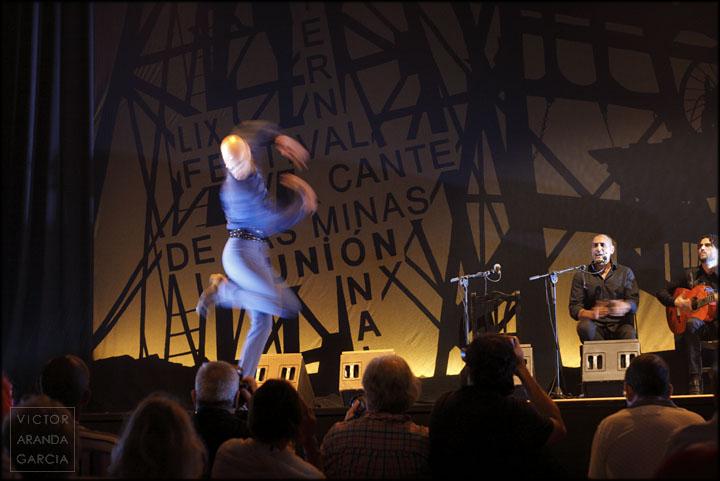 Fotografía del bailarín Hugo López en movimiento en el escenario