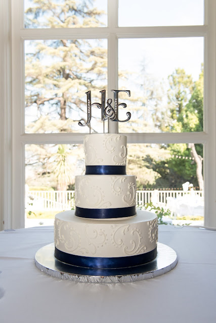 Our Kellogg House Wedding and Reception was absolutely beautiful. The backyard was perfect with white linens and bistro lights over the yard. We had a beautiful white cake with a navy blue ribbon.