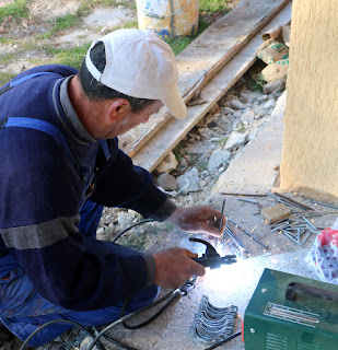 Bekir welding big nails onto the clamps