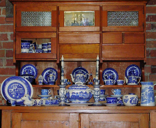 An old kitchen cupboard with Hoosier Top displaying a collection of Blue Willow china.