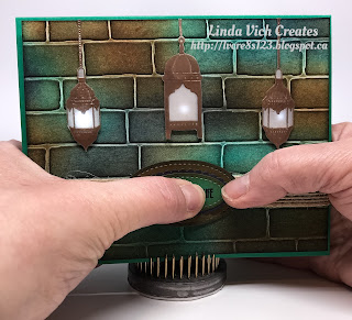 Linda Vich Creates: You Light Up My Life Lighted Card. A multicolored brick background showcases three copper embossed lanterns that light up when the sentiment is pressed.