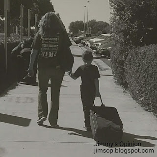 Black and white photo of my wife Cindy walking away with our grandson Benjamin pulling his luggage behind.