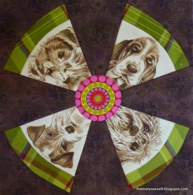 Four brown and cream dog faces form the blades of this propeller shape. The outer band is a green plaid.