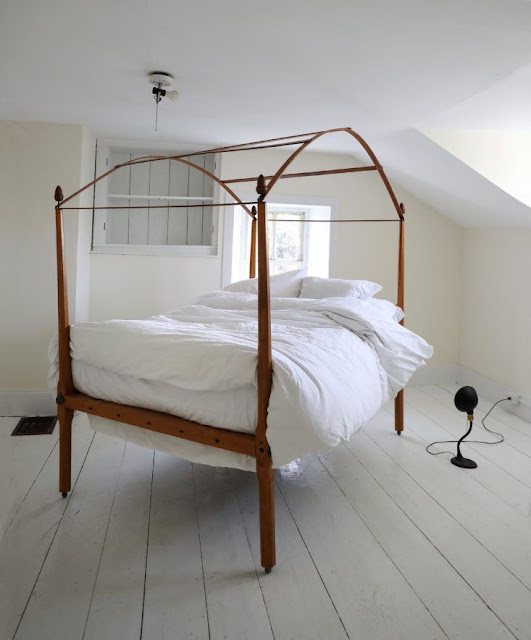 Minimal wood canopy bed in white farmhouse bedroom with white painted floor - found on Hello Lovely Studio