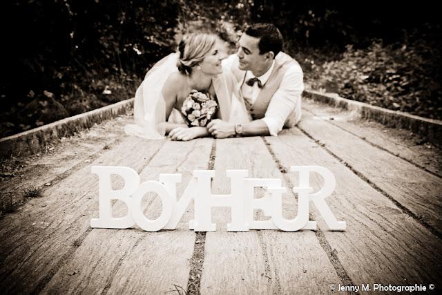 photo mariés allongés sur pont de bois et mot bonheur