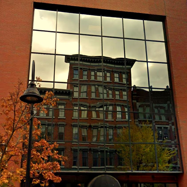 glass storefront reflects image of red brick victorian building with gray stone trim