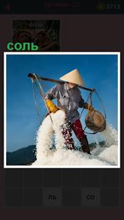 мужчина в ведрах собирает соль и высыпает в определенное место