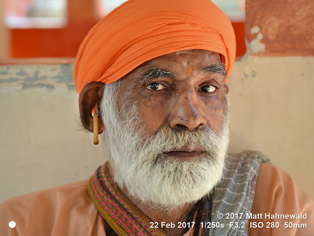 matt hahnewald photography; facing the world; gorakh nath; monk; monastery; bhavnath; bhavnath fair; character; face; earrings; ears; holed; eyes; facial expression; eye contact; full beard; turban; orange; consent; empathy; rapport; respect; traveling; religious; traditional; cultural; hinduism; festival; event; mela; devotee; pilgrim; junagadh; gujarat; asian; indian; western india; one person; male; old; man; picture; photo; face perception; physiognomy; educational; nikon d3100; nikkor af-s 50mm f/1.8g; prime lens; 50mm lens; 4x3 aspect ratio; horizontal orientation; street; portrait; closeup; headshot; three-quarter view; outdoors; color; posing; authentic; powerful; determined; focused; manly; kanphata; yogi; darshani; gorakhnathi; shaivism; trimmed; neat; splitted ears