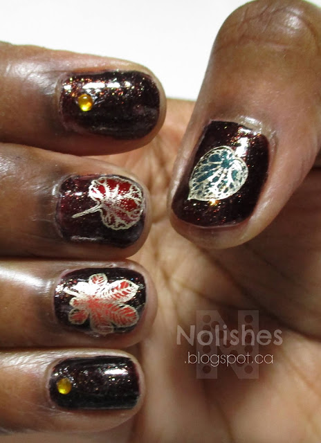 Brown manicure using advanced stamping technique to apply coloured leave decals to accent some of the fingers. Amber coloured gems are used on accents for the other fingers.