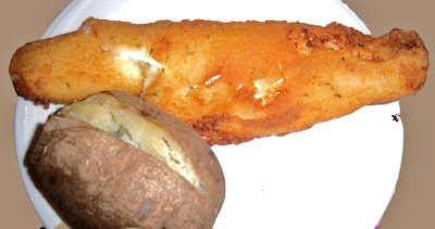 this is a white plate with fried haddock on it and potato