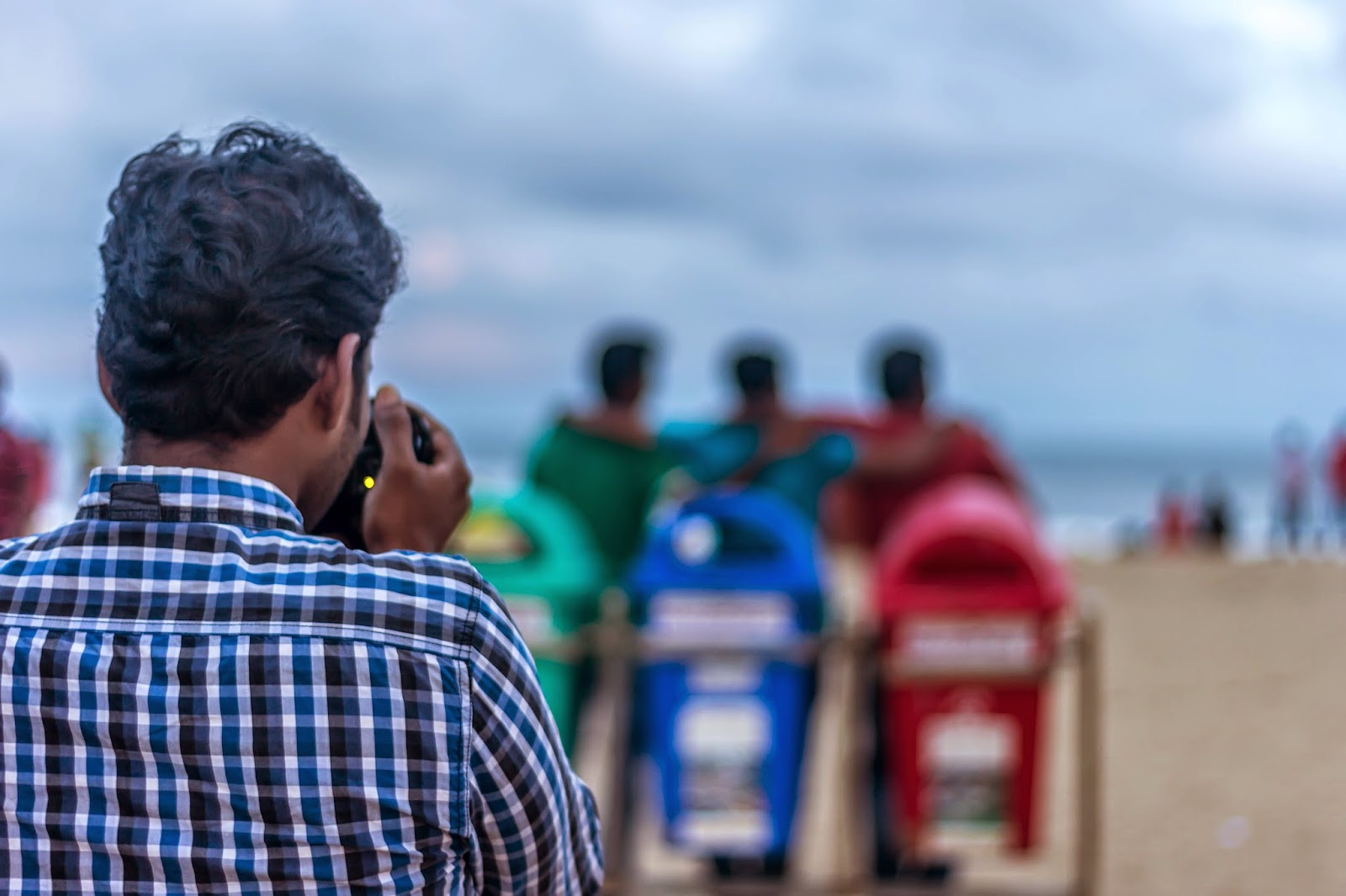 Photo of a photographer taking picture of three guys standing behind three dustbins in a public beach