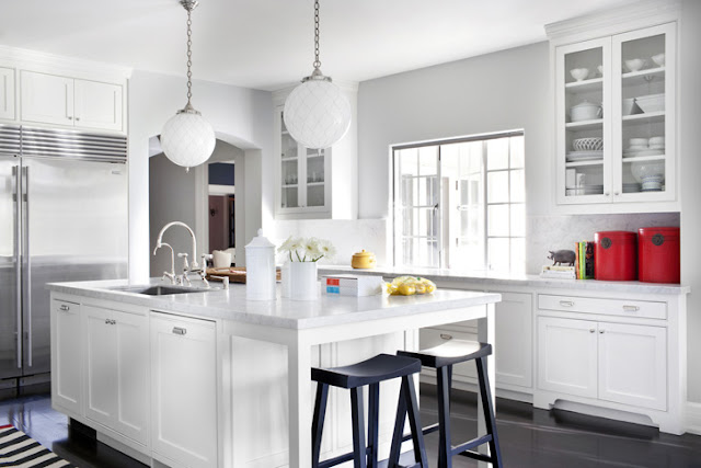 White kitchen with marble counters, glass upper cabinets and glass pendant lights with black stools in a Beverly Hills home