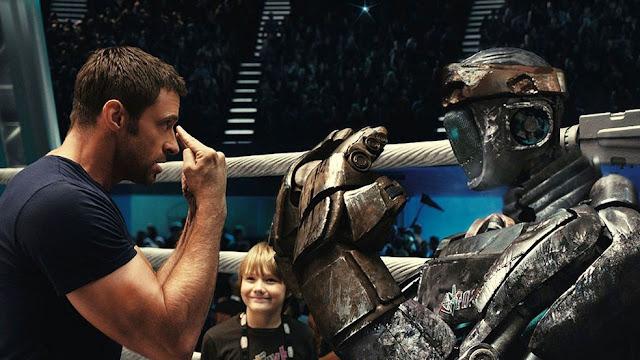 """Hugh Jackman enseñando al robot Atom ante la mirada de admiración de su """"hijo"""" Max (Dakota Goyo)."""