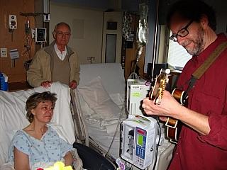 A friend entertaining a patient at the hospital as the husband looks on