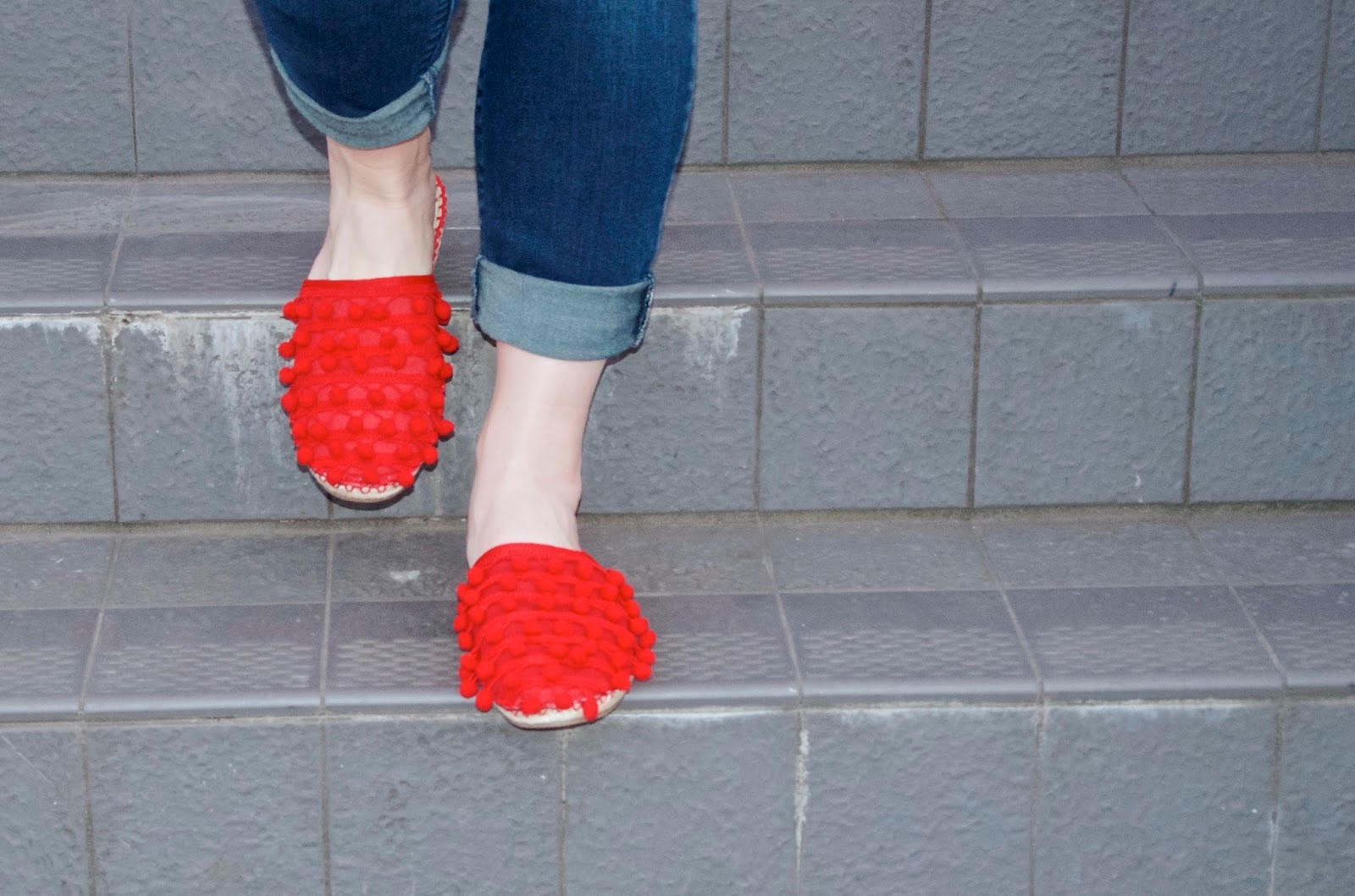 rolled up jeans, red pom pom espadrilles and stairs