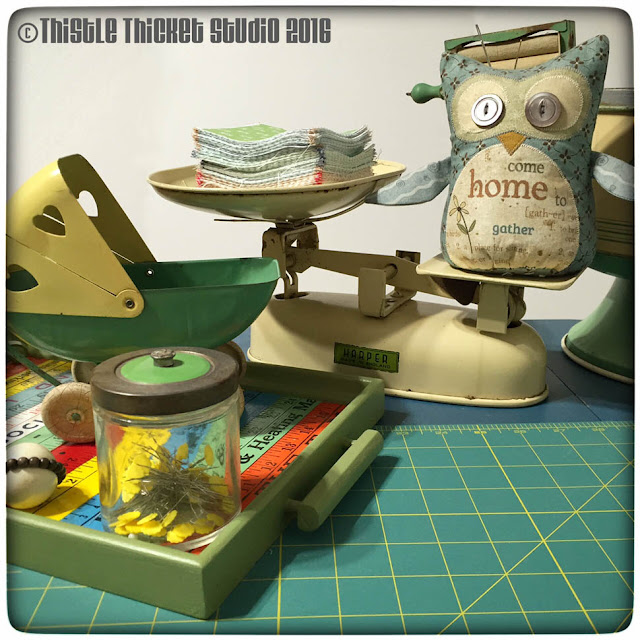 Thistle Thicket Studio, cutting table, vintage scale, Home To Roost owl pincushion, vintage baby buggy, yardstick tray
