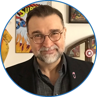 photo of Blam, a man with brown hair, salt-and-pepper beard, and glasses, wearing a gray shirt and black jacket with pink pin on lapel, only head and shoulders visible, standing in front of a wall decorated with various comics art