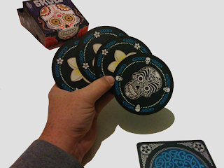 The four blue cards fanned out in a player's hand. The box, with it's Mexican folk art style artwork, is visible in the background. The design of the score mat is partially visible. The skull card, on the right in the player's hand, is covered with black lines and swirls. The flower cards are partially obscured, but you can see enough to tell that it's a white five-petaled flower.