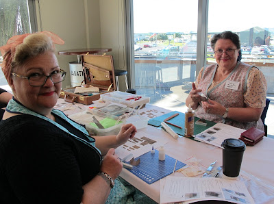 Two women dressed in 1940s outfits, crafting on a table at a workshop.