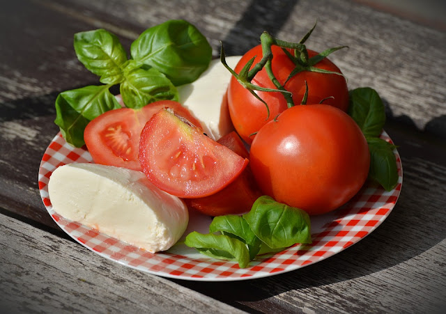 a plate of summer tomatoes, basil, and mozzarella cheese