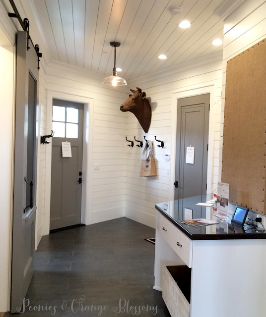 Touring a French farmhouse - a mudroom with shiplap walls, grey doors, and country touches