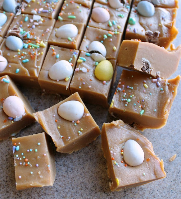 squares of just cut peanut butter fudge with chocolate eggs on the cutting board