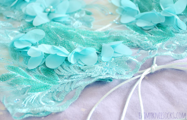 Details on the handmade teal Mia 3D lace halter crop top by Charlotte Martin LDN, featuring sequined embroidery, floral applique, a lattice-style backless design, and sheer mesh bodice.