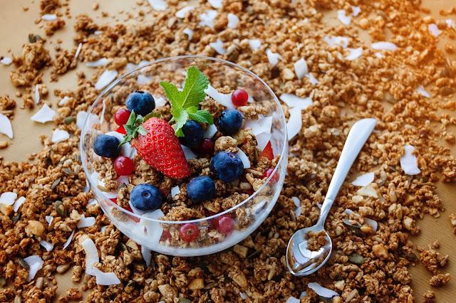 Tazón de cereales con arándanos, una fresa en una mesa cubierta de más cereales