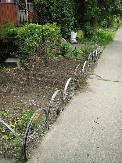 Roda sepeda bekas dijadikan pagar di depan rumah.