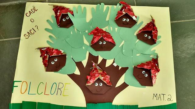 Painel Folclore com dobraduras de Sacizinhos e árvore de recorte de contorno de mãos.